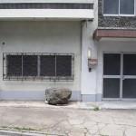 正面玄関。置いてある石や錆びついた格子がレトロ